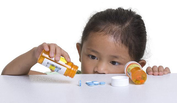 A young girl looks at a pile of pills that was left on a counter.Thinkstock